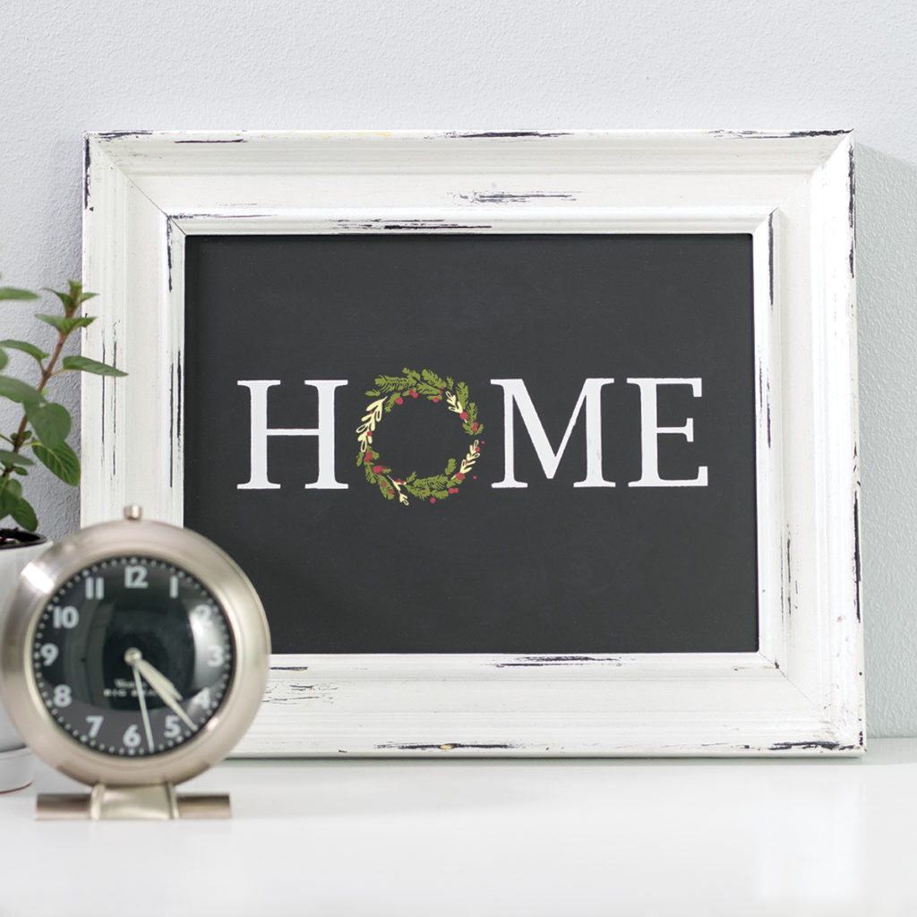 """Home décor showing white framed chalkboard with the word """"Home"""" chalked on it and desk clock in foreground."""