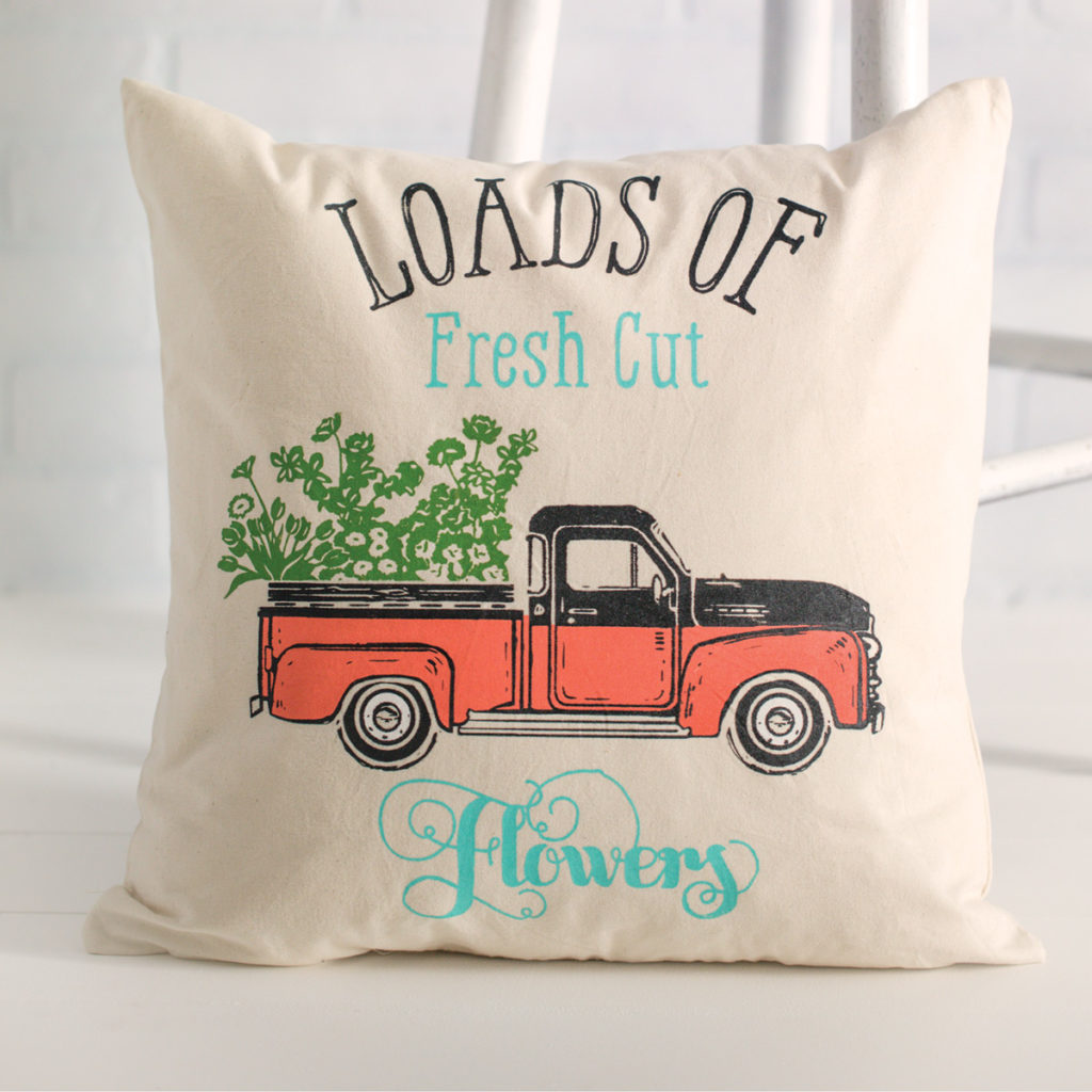 """Pillow with vintage truck and """"loads of fresh cut flowers"""" inked on it."""