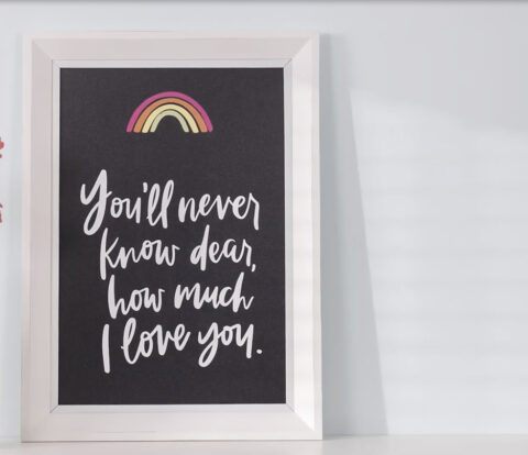 You'll Never Know Dear Transfer design on 12x18 chalkboard next to vase of pink daisies