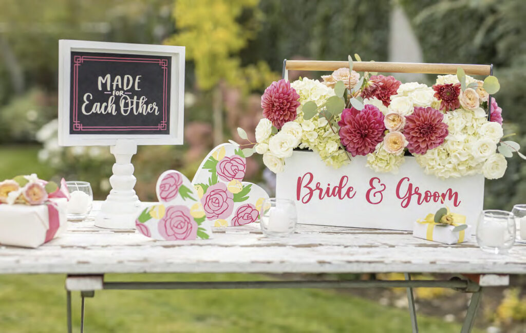 A rustic wedding display with floral hearts and a handled box with pink and cream flowers with words bride and groom